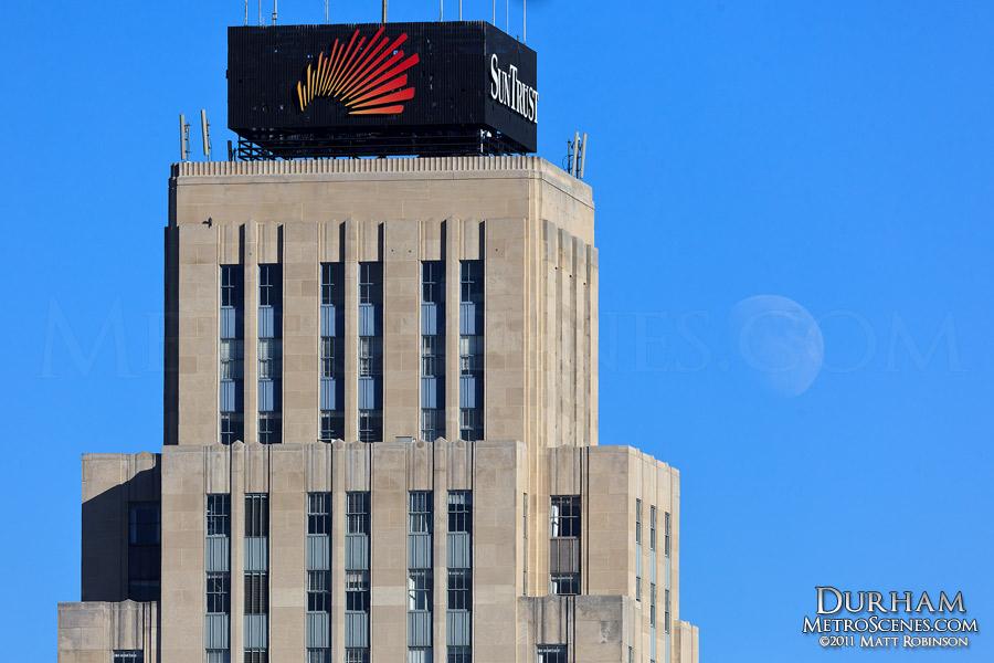 Daytime moonrise behind Durham's Hill Building (SunTrust Tower)