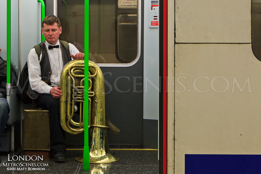 Man with tuba on the District Line, London
