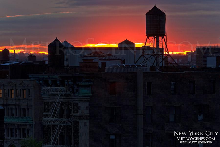 Sunrise behind New York City water tower