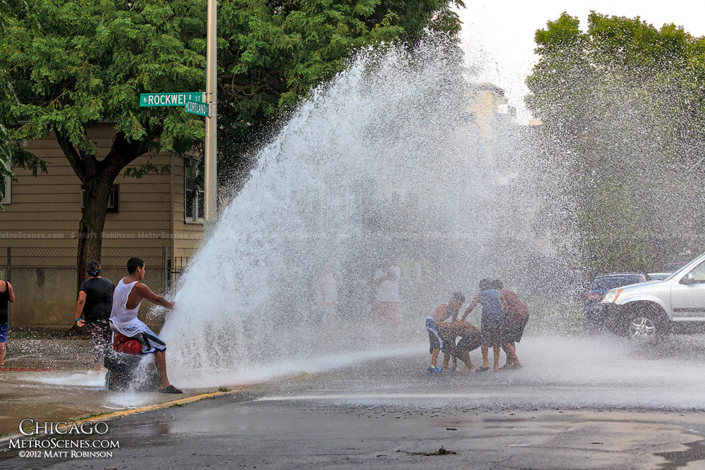 Children play in an opened fire hydrant at Rockwell and Cortland