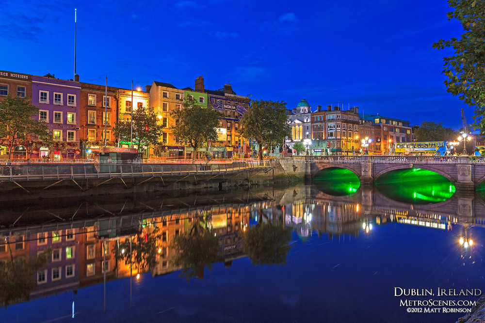 Buildings reflect on the still River Liffey at night