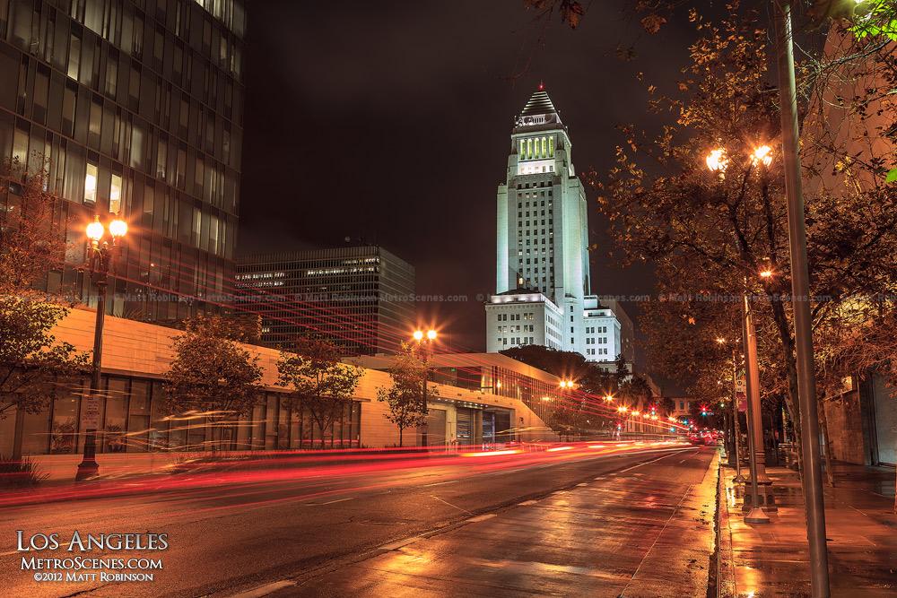 Brake lights stream down Main Street with Los Angeles City Hall at night