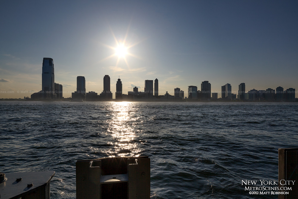 The sun hovers of Jersey City from Manhattan