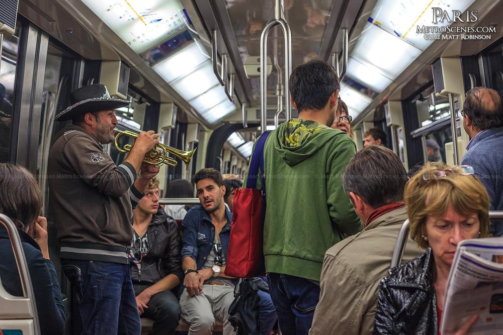 Musician plays a cornet aboard a Paris Metro train
