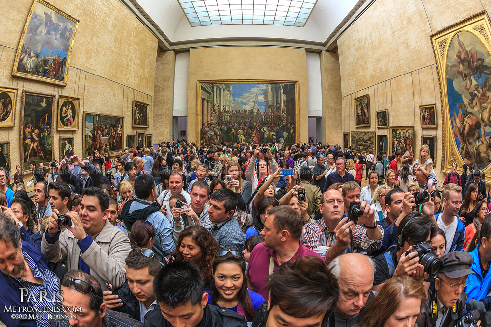 Visitors crowd around to photograph the Mona Lisa at the Lourve