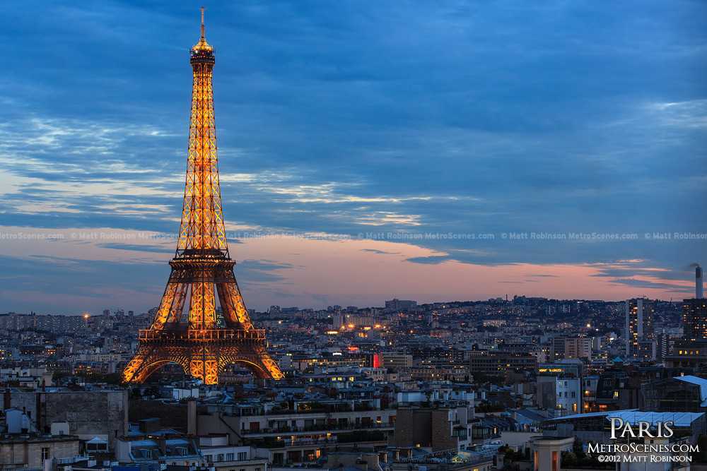 Eiffel Tower rises above Paris at night from the Arc de Triomphe