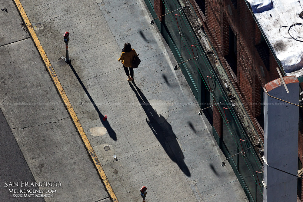 A long shadow follows a pedestrian