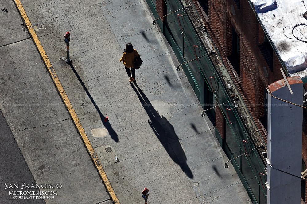 A long shadow follows a pedestrian
