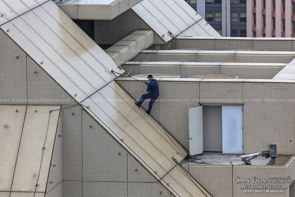 A man rappels up the slanted Nikko Hotel roof in San Francisco