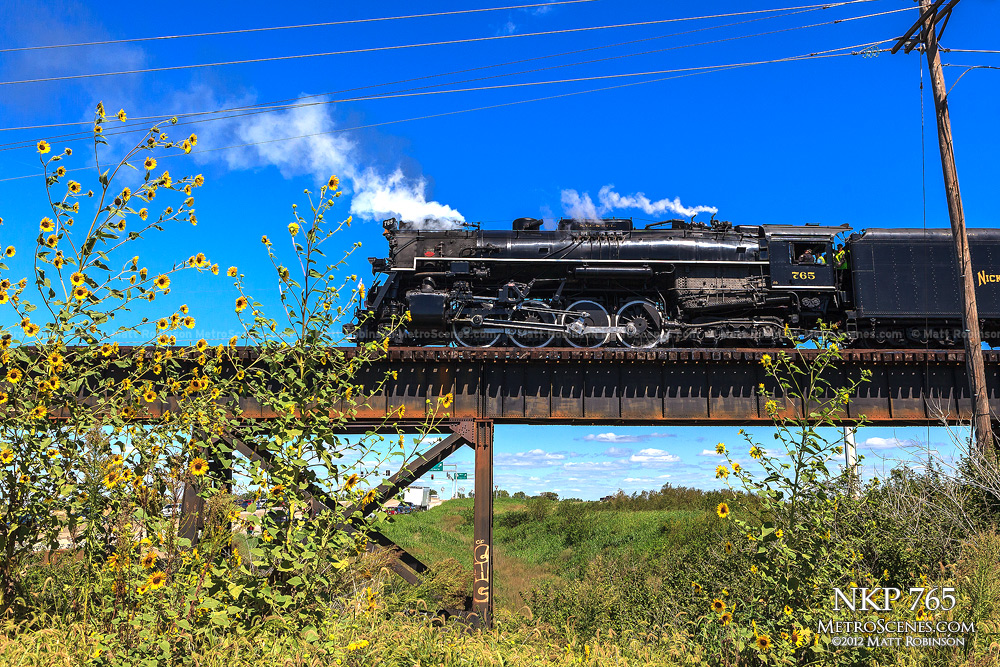 NKP 765 with yellow flowers backing across the Missouri River Bridge