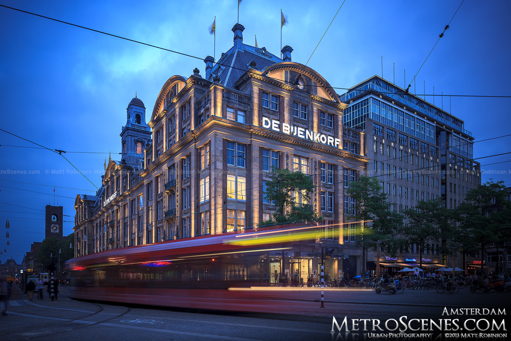 A tram streams past De Bijenkorf at dusk in Amsterdam