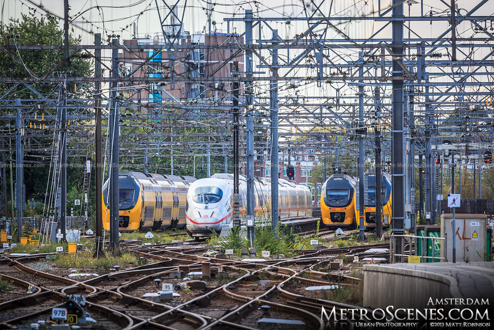 Train tracks leading out of Amsterdam with Intercity and ICE train