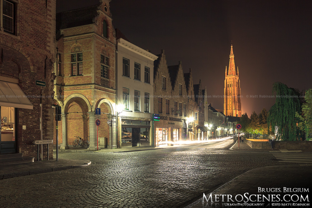 Illuminated spire of Church of Our Lady at night in Bruges