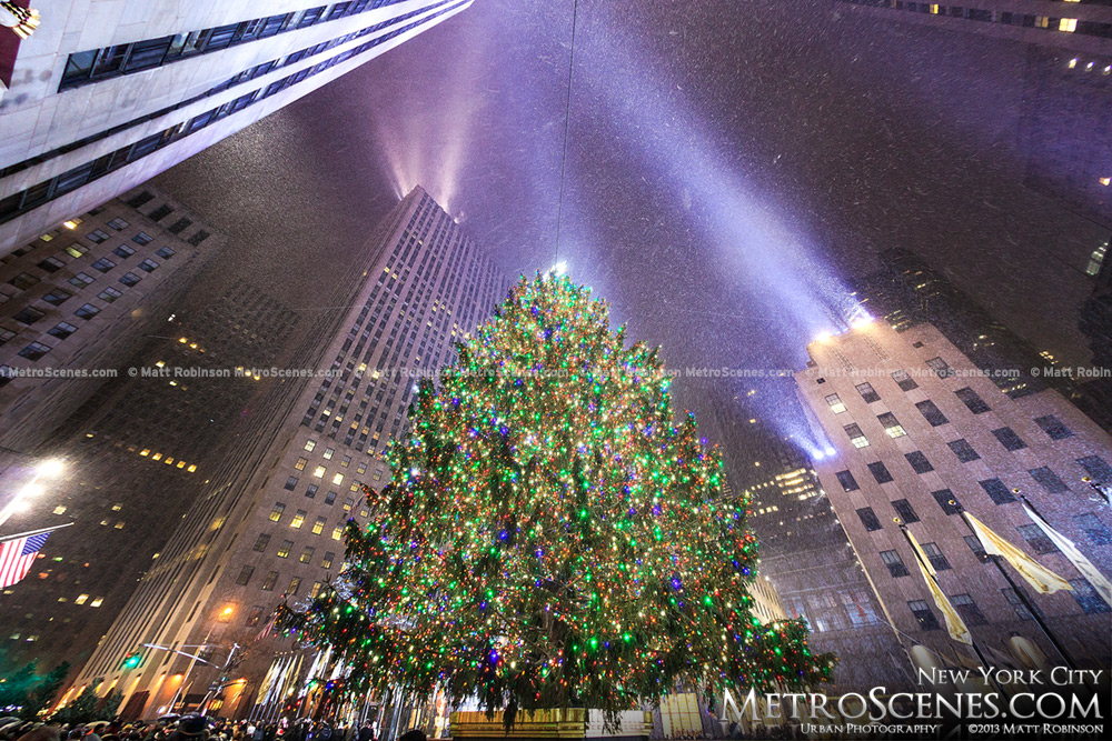 Wide Angle view of Rockefeller Center Christmas Tree with snow and light beams