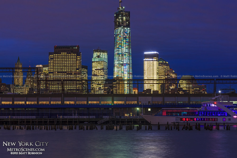 World Trade Center rises above Pier 40 from Hudson River Park at night