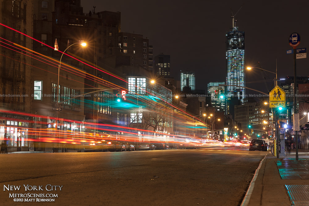 Traffic streams down Seventh Avenue at Charles Street with One World Trade