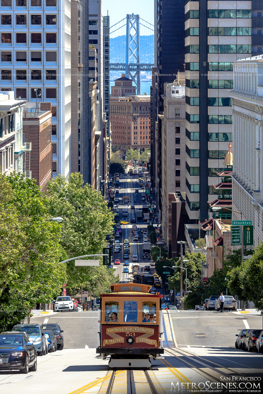 San Francisco cable car makes its way up California Street with the Bay Bridge