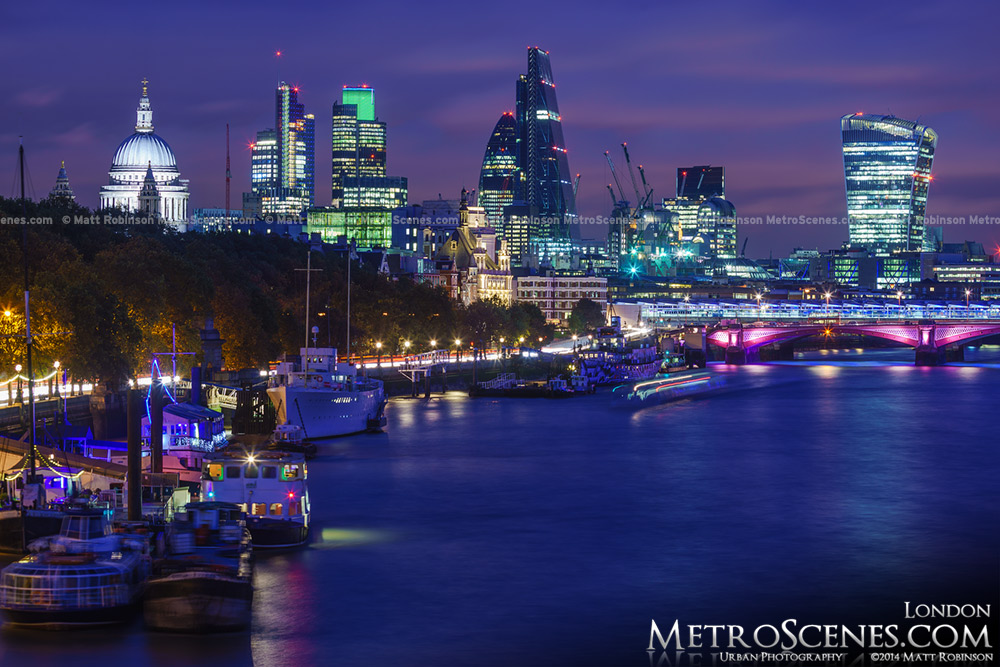 Boats moored on the Thames with the London Skyline