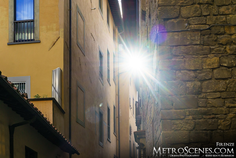 Sun peeks through buildings in Florence