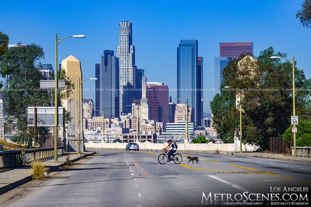 Man and Dog cross Whittier Boulevard with downtown LA