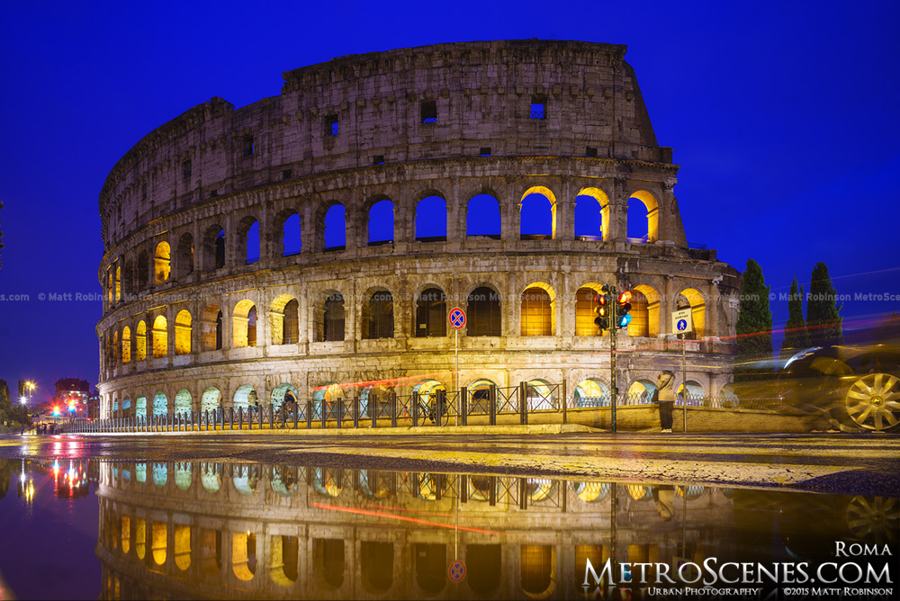 The Colosseum at night with puddle reflection
