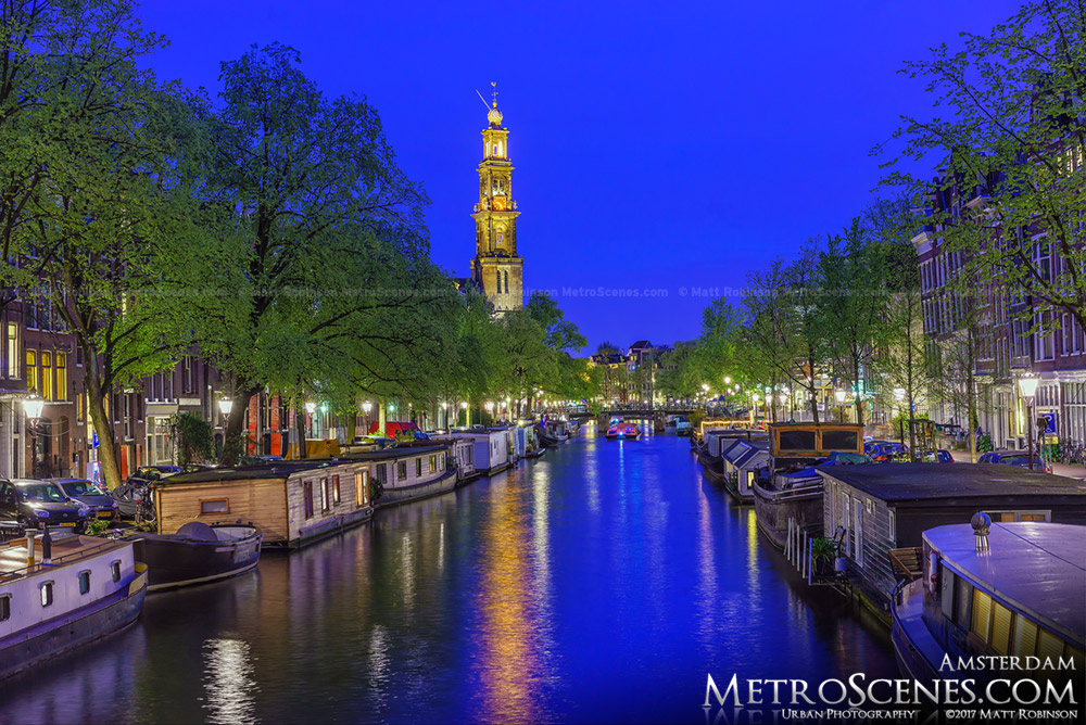 Houseboats on Prinsengracht Canal at night with Westerkerk