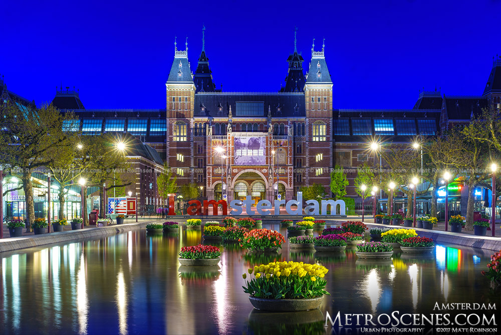 Rijksmuseum at night with I Amsterdam sign and tulips