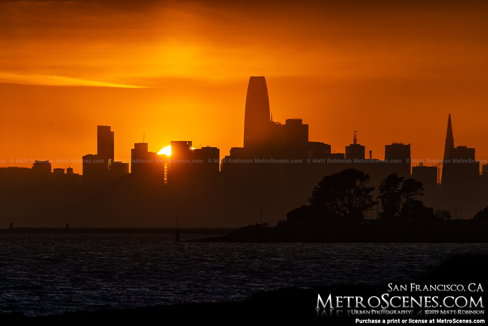 The sun sets behind San Francisco from Alameda